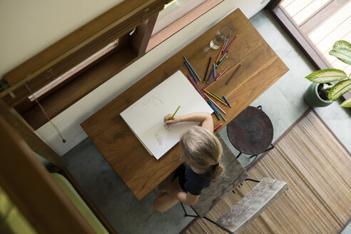 Little girl sitting at table drawing with crayons - SBOF00857