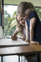 Mother and daughter drawing with crayons - SBOF00860