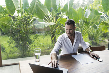Mature man sitting at table in front of lush garden, using laptop - SBOF00869