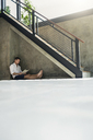 Mature man sitting under staircase, reading a book - SBOF00872