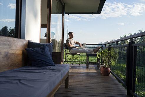 Man sitting on balcony of modern house looking landscape, holding laptop - SBOF00875