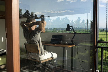 Mature man sitting at desk, looking at view - SBOF00878