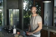 Mature man standing in kitchen, preparing healthy breakfast - SBOF00884