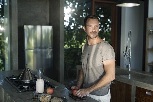 Mature man standing in kitchen, preparing healthy breakfast - SBOF00884