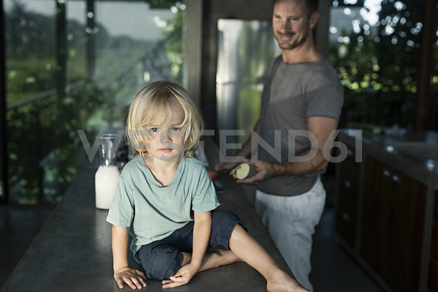 Son sitting on counter in kitchen while father is preparing breakfast - SBOF00887 - Steve Brookland/Westend61