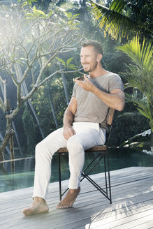 Mature man sitting barefoot by the poolside, talking on the phone - SBOF00893