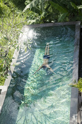 Man swimming diving under water in swimming pool - SBOF00902