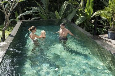 Happy family having fun , playing in swimming poo, in summer - SBOF00905