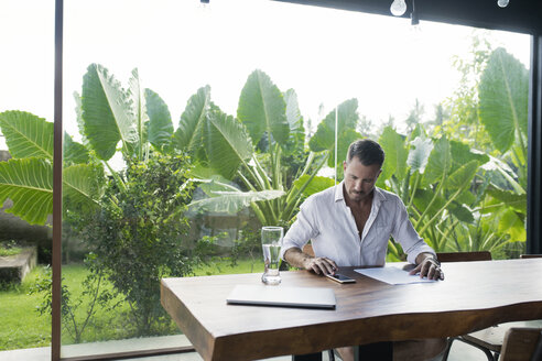 Mature man sitting at table in front of lush garden, writing - SBOF00908