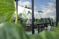 Mature man sitting at table in front of lush garden, relaxing - SBOF00911