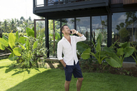 Mature man walking in garden in front of modern villa, using smartphone - SBOF00914