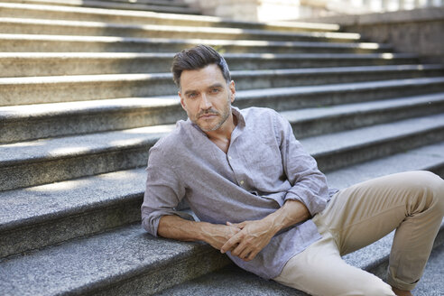 Portrait of serious mature man sitting on stairs - PNEF00311