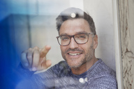 Portrait of smiling man behind glass pane wearing glasses pointing on viewer - PNEF00326