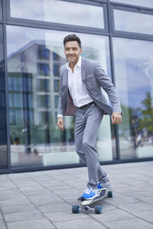 Portrait of smiling businessman skateboarding on pavement - PNEF00332
