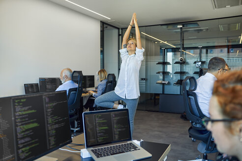 Woman practicing yoga in office surrounded by busy colleagues - ZEDF00972