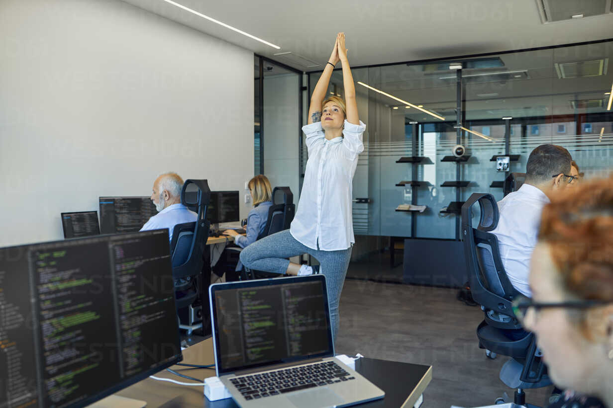 Woman practicing yoga in office surrounded by busy colleagues - ZEDF00972 - Zeljko Dangubic/Westend61