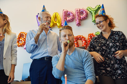 Colleagues having a birthday celebration in office with party blower and party hats - ZEDF00975