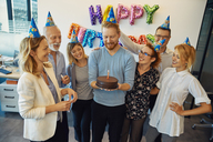 Colleagues having a birthday celebration in office with cake and party hats - ZEDF00978