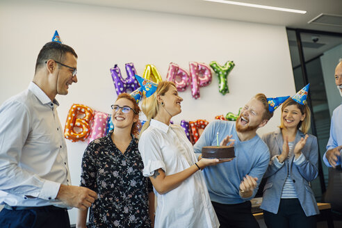 Colleagues having a birthday celebration in office with cake and party hats - ZEDF00984