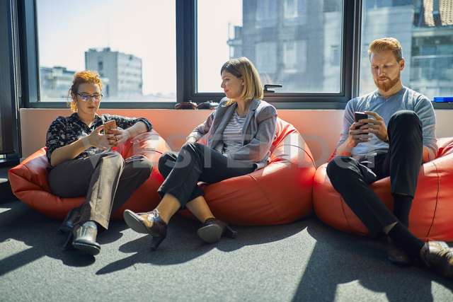 Colleagues with cell phones sitting in bean bags in office lounge - ZEDF00987