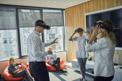 Colleagues wearing VR glasses in office - ZEDF00990