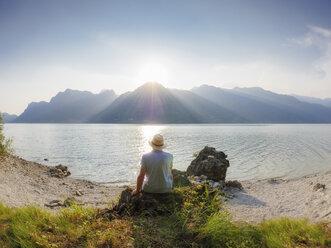 Italy, Lombardy, back view of man sitting at Lake Idro at sunset - LAF01946