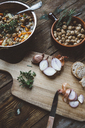 Mediterranean soup in copper pot, bowl of croutons and ingredients on wooden board - GIOF03293