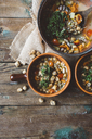 Mediterranean soup in copper pot and terracotta bowls on wood - GIOF03296