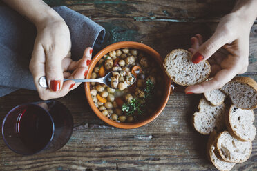 Woman eating Mediterranean soup with bread, close-up - GIOF03299
