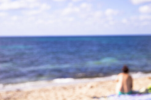 Blurred back view of woman sitting on the beach looking at view - CMF00745