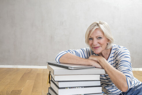 Portrait of smiling senior woman leaning on stack of books and laptop - FMKF04621