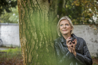 Portrait of smiling senior woman with coffee mug leaning against tree trunk - FMKF04624