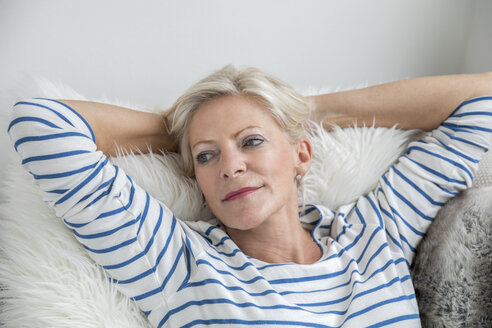 Portrait of senior woman relaxing on couch at home - FMKF04633