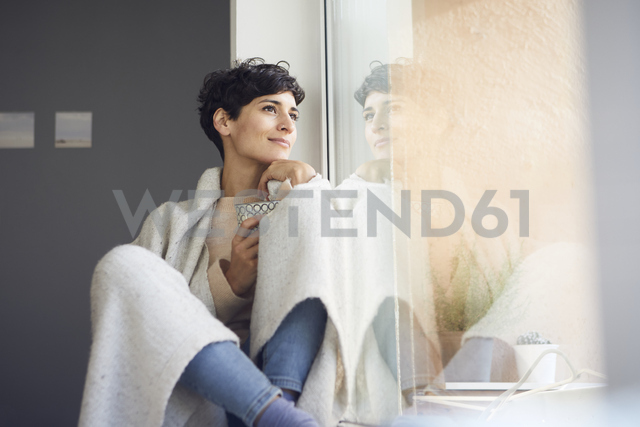 Relaxed woman at home sitting at the window - RBF06102 - Rainer Berg/Westend61