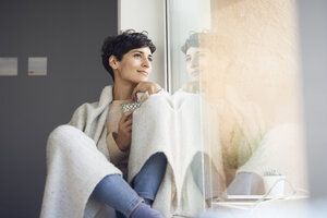 Relaxed woman at home sitting at the window - RBF06102