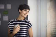 Smiling woman with cup of coffee looking out of window - RBF06105