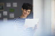 Smiling woman with tablet at the window - RBF06108