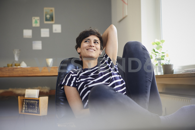 Smiling woman sitting at home relaxing - RBF06114