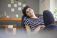 Portrait of smiling woman sitting at home relaxing - RBF06117