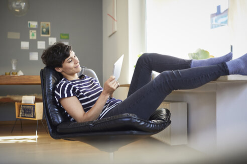 Relaxed woman using tablet at home - RBF06120