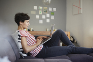Woman using laptop on couch at home - RBF06129