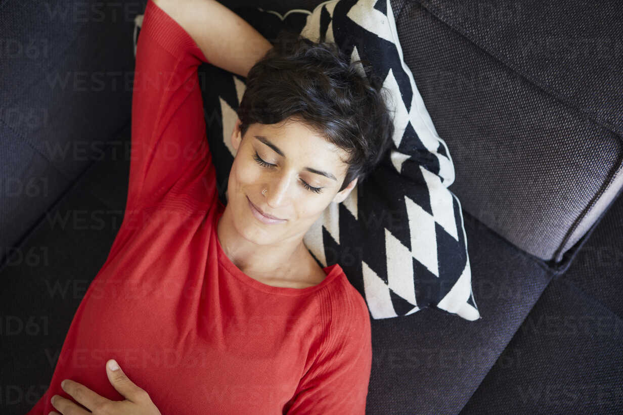 Smiling woman lying on couch at home with closed eyes - RBF06135 - Rainer Berg/Westend61