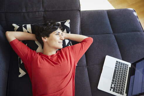 Woman lying on couch at home next to laptop - RBF06138