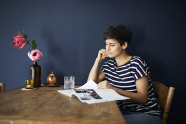 Woman at home sitting at wooden table reading a magazine - RBF06141