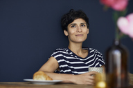 Portrait of smiling woman at home sitting at wooden table - RBF06144
