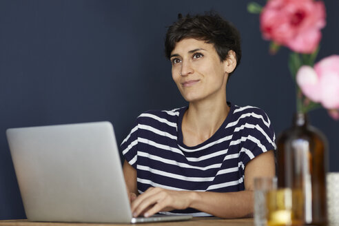 Portrait of smiling woman at home sitting at wooden table using laptop - RBF06147