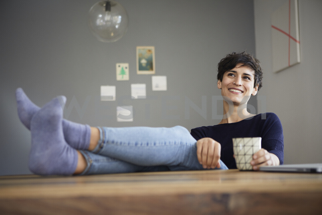 Smiling woman at home sitting at table with cup of coffee - RBF06159