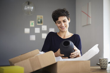 Smiling woman unpacking parcel at home - RBF06162