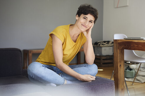 Portrait of smiling woman sitting on couch at home - RBF06165