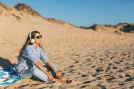 Portugal, Aveiro, woman sitting near beach dune listening music with headphones - JPF00276